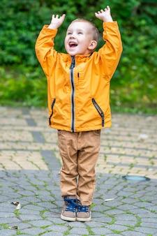 ハンスアップと公園の歩道に立っている幸せな笑顔の白人の子供