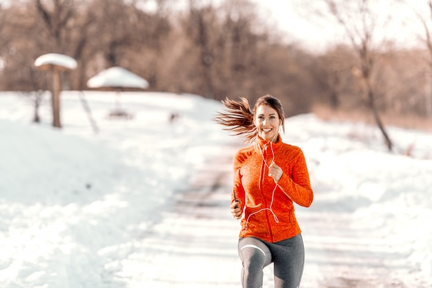 イヤホンでトレイルの上に立って、音楽を聴いてスポーツウェアで幸せな笑顔の白人女性。冬のフィットネスの概念。