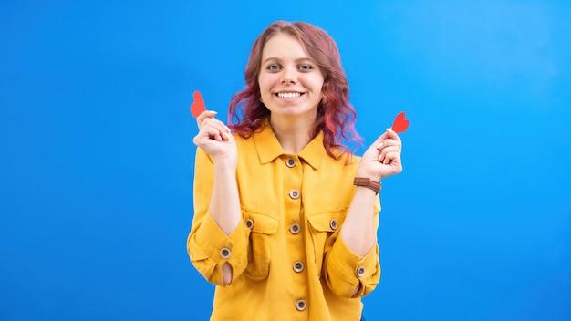 Счастливая улыбающаяся кавказская женщина с двумя красными сердцами