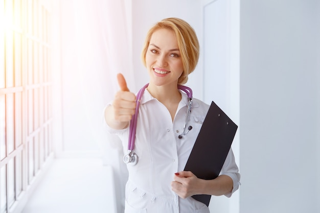 Счастливый улыбающийся веселый женщина-врач с большими пальцами руки вверх жест. портрет улыбается женщина-врач со стетоскопом и доской сзажимом для бумаги. солнечный свет