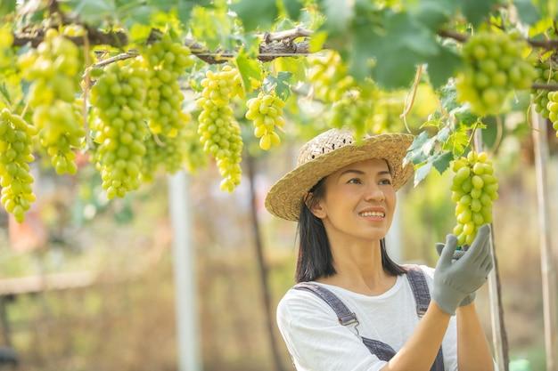 オーバーオールとファームドレスの麦わら帽子を身に着けている幸せな笑顔の陽気なブドウ園の女性