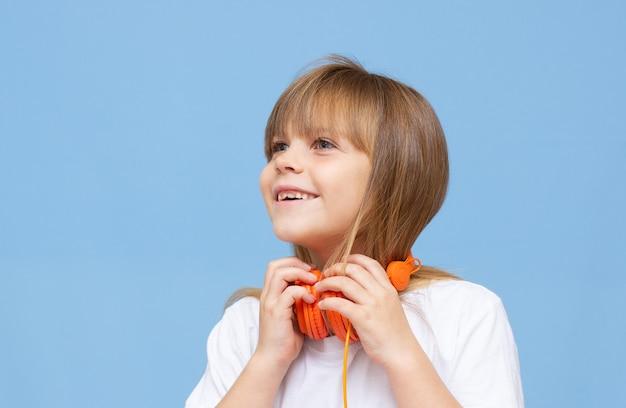 幸せな笑顔の子供は、カラフルなブルーの背景の上にヘッドフォンで音楽を聴いて楽しんでいます。鮮やかで楽しい感情、喜びの幸せな子供はヘッドフォンで歌を聴きます