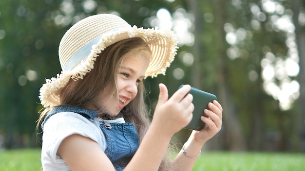 Happy smiling child girl looking in mobile phone outdoors in summer.