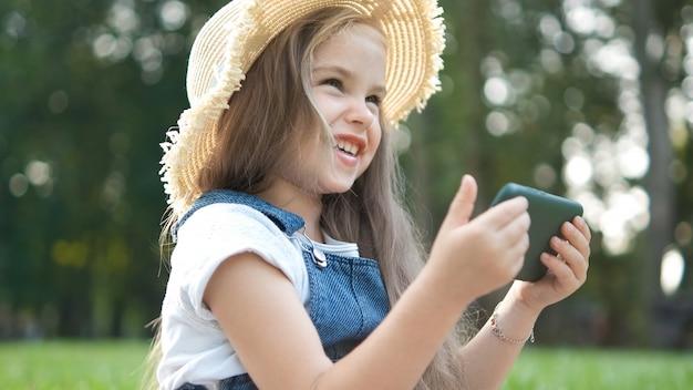 여름에 야외에서 그녀의 휴대 전화에서 보고 행복 웃는 아이 소녀.