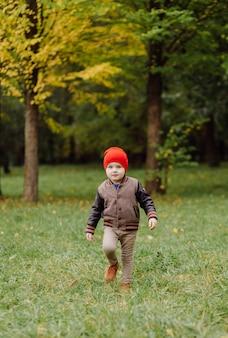 Bambino sorridente felice che gioca all'aperto in un giardino