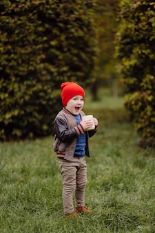 Счастливый улыбающийся ребенок, играющий на открытом воздухе в саду