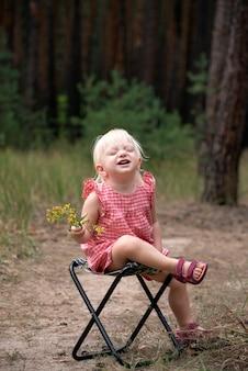 ワイルドフラワーと幸せな笑顔の子供。森の中で手に花と椅子に座っているブロンドの女の子。夏の気分。