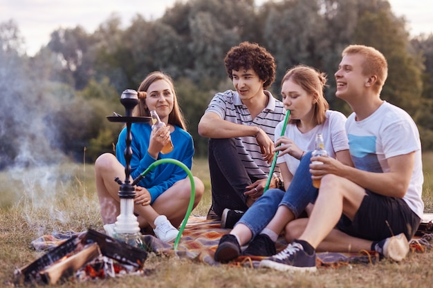 Happy smiling company have picnic together, smoke hookah, sits near bonfire, communicate with each other, drink non alcoholic drinks, have satisfied expressions. friends and leisure time concept