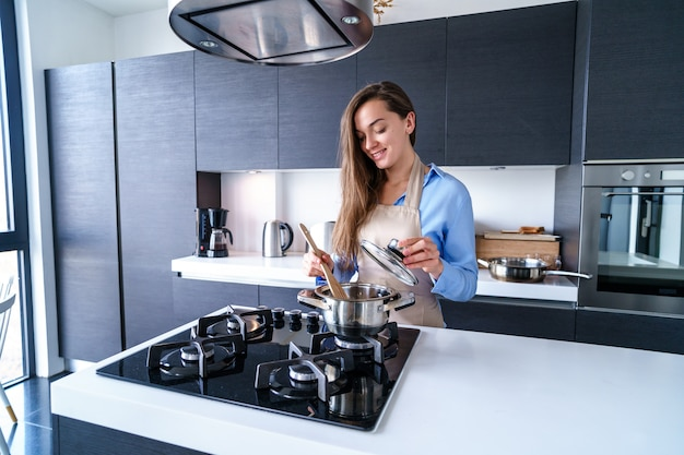 Happy smiling cooking woman housewife in apron using steel metal saucepan for preparing boiled dishes for dinner in the kitchen at home. kitchenware for cooking