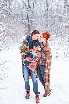 겨울 하얀 눈 덮인 숲, 전체 길이 초상화에 강아지와 함께 격자 무늬 산책으로 덮여 행복 한 미소 커플