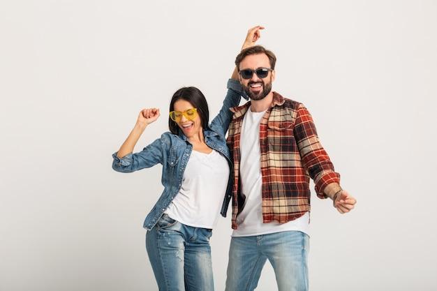 白いスタジオで隔離のパーティーで踊る幸せな笑顔のカップル