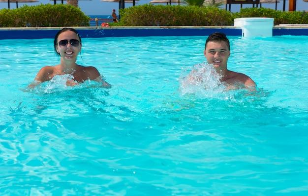 화창한 여름날 호텔 수영장에서 아쿠아 피트니스를 하는 행복한 미소 커플
