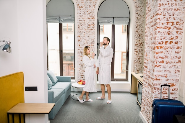 Happy smiling couple drinking champagne while standing in hotel room or appartment. valentine's day or birthday. home or hotel bedroom.
