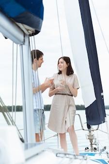 야외 보트 파티에서 보드카 칵테일을 마시는 행복한 미소 짓는 커플, 명랑하고 행복합니다. 바다 여행, 청소년, 여름 휴가 개념에서 즐거운 시간을 보내는 젊은이들. 술, 휴가, 휴식, 사랑.