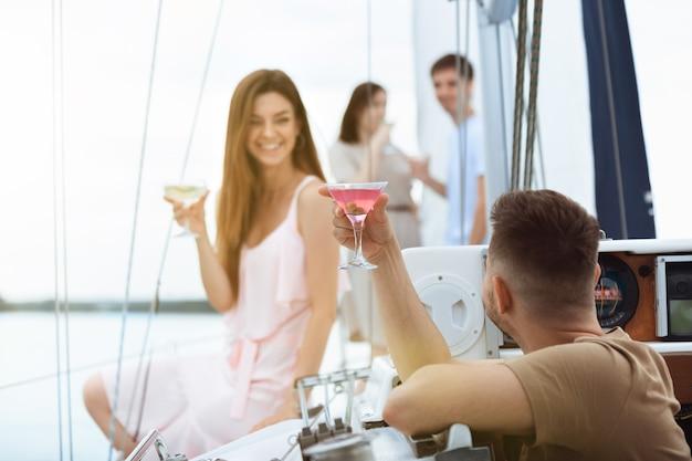 屋外のボートパーティーでウォッカカクテルを飲む幸せな笑顔のカップル、陽気で幸せ。海のツアー、若者と夏休みのコンセプトを楽しんでいる若者。アルコール、休暇、休息、愛。