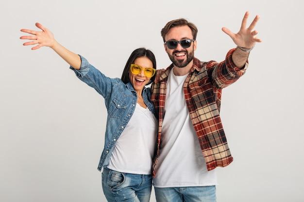 白いスタジオで隔離のカメラで手をつないで幸せな笑顔のカップル