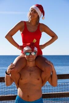 愛の幸せな笑顔のカップルは、紅海でクリスマスと新年を祝います。