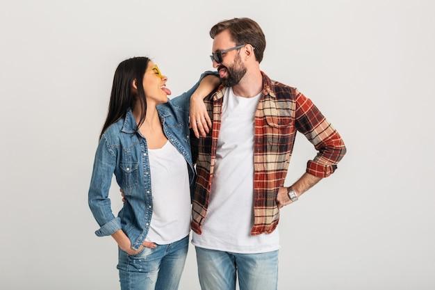 白いスタジオの背景、スタイリッシュな男と女に分離された幸せな笑顔のカップル