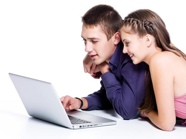 Счастливая улыбающаяся пара с интересом смотрит на ноутбук - изолированные на белом