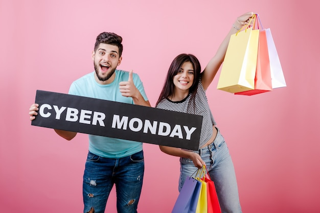 Happy smiling couple man and woman with cyber monday sign and colorful shopping bags