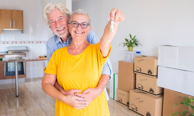 Счастливая улыбающаяся пара пожилых людей с белыми волосами, обнимающаяся с ключами от новой пустой квартиры с движущимися ящиками на полу - концепция активных пожилых людей и новое начало, как пенсионер