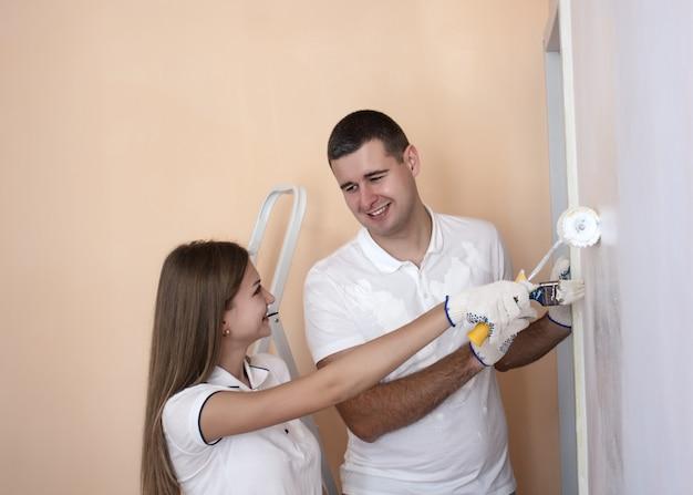 Счастливая улыбающаяся пара, расписывающая внутреннюю стену нового дома или квартиры они держат инструменты