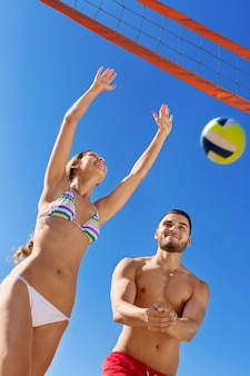 Happy  smiling  couple playing volleyball