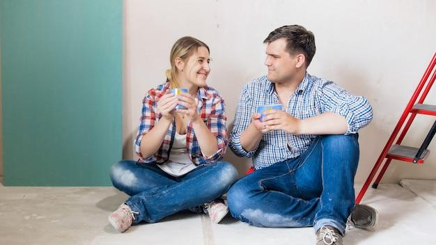 행복 한 미소 커플 바닥에 앉아서 홈 리 모델링에서 휴식 시간 동안 커피를 마시는.