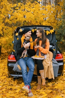 A happy, smiling couple of travelers drink coffee or tea while sitting on the trunk of a car in the autumn forest with their pet