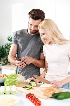 Happy smiling couple using mobile phone to find a recipe