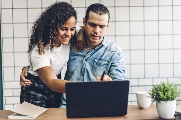幸せな笑顔のカップルが一緒にラップトップコンピューターでの作業。創造的なビジネスカップルの計画と自宅のリビングルームでのブレーンストーミング