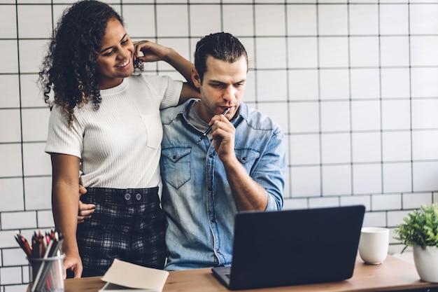 幸せな笑顔のカップルが一緒にラップトップコンピューターで作業します。創造的なビジネスカップルの計画と自宅のリビングルームでブレーンストーミング