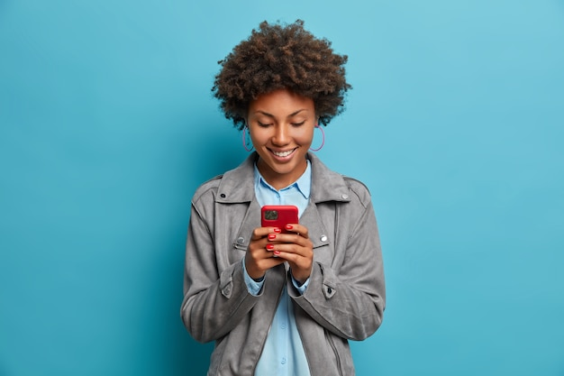 Happy smiling curly haired young woman types message on mobile phone, looks with glad expression at display, wears grey jacket,