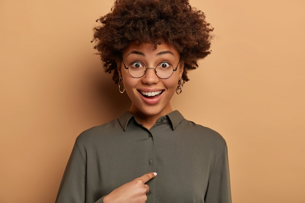 Happy smiling curly woman surprised someone mentioned her name, points at herself, didnt expect to win or being chosen, asks boss whether exactly she is promoted, wears round glasses and shirt.