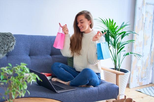 幸せな笑顔かわいい嬉しい満足した楽しい買い物中毒の女性はオンラインでギフトを受け取り、紙の色のバッグを保持しています