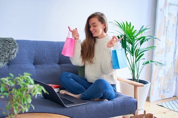 Happy smiling cute glad satisfied joyful shopaholic woman received gifts online and holds paper colored bags