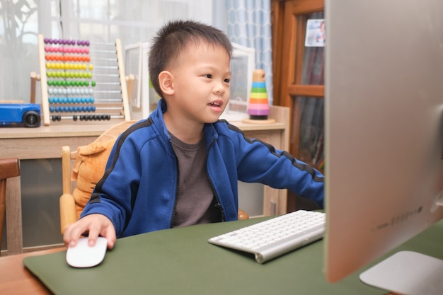 Happy smiling cute little asian kid with personal computer making video call at home, kindergarten boy studying online, attending school via e-learning