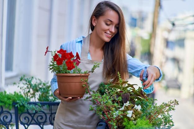 植木鉢ペチュニアを保持し、バルコニーの植物の世話をするエプロンを身に着けている幸せな笑顔のかわいい女性の庭師
