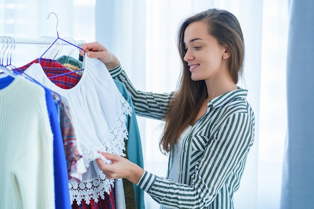 幸せな笑みを浮かべてかわいい若いブルネットの女性の洋服の買い物と着用する服を選択中にモダンなトレンディなスタイリッシュな女性服の完全なワードローブラックの近くに立って
