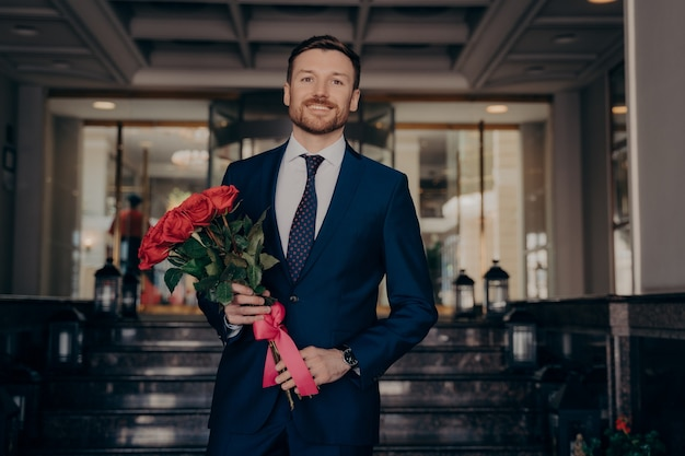 Happy smiling dapper dressed handsome businessman wearing blue suit, holding bouquet of fresh red roses with ribbon, waiting for girlfriend with smile, standing alone in front of hotel lobby entrance
