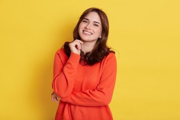 즐거운 외모와 함께 행복 한 미소 어두운 머리 여자, 부담없이 입고, 이빨 미소로보고, 턱 아래에 주먹을 유지, 노란색 벽 위에 절연 서.