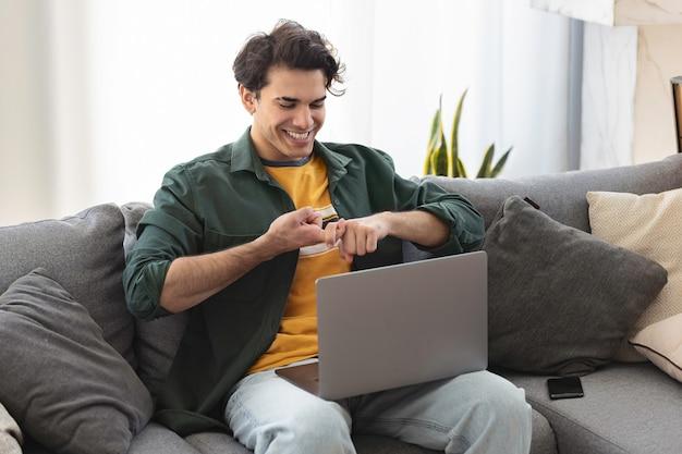 Счастливый улыбающийся глухой молодой кавказский мужчина использует язык жестов во время видеозвонка с помощью ноутбука, сидя на диване у себя дома