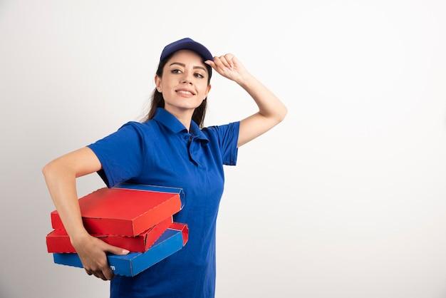 白い背景の上のテイクアウト ピザ ボックスと青い制服を着た幸せな笑顔の配達の女の子。高品質の写真