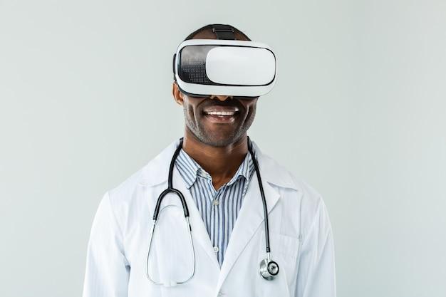 Счастливый улыбающийся врач в очках vr, стоя у стены