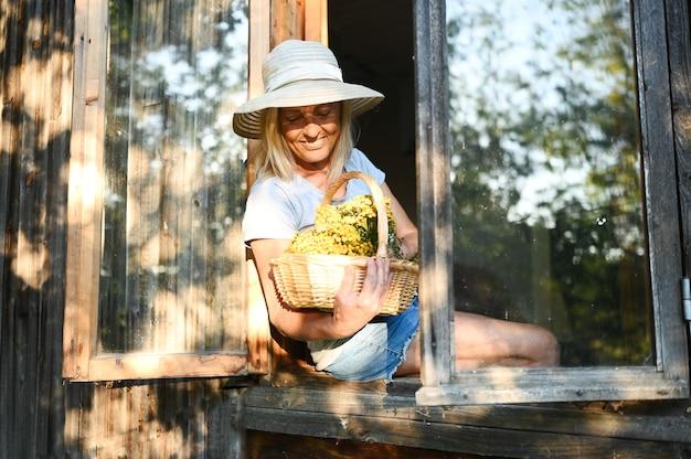 Счастливая улыбающаяся эмоциональная старшая женщина позирует у открытого окна в старом деревянном деревенском доме в соломенной шляпе с цветочной корзиной