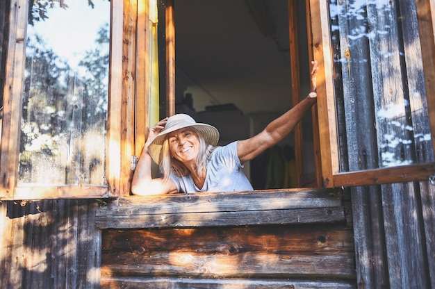 Happy smiling emotional senior woman posing by open window in old wooden village house in straw hat.