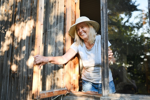 Happy smiling emotional senior woman posing by open window in old wooden village house in straw hat
