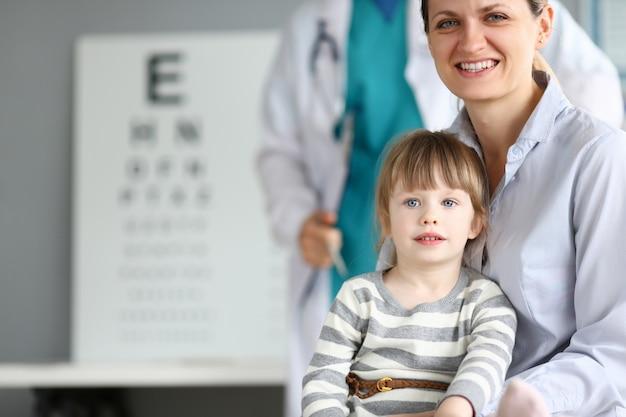 子供の医者のオフィスで幸せな笑顔の家族
