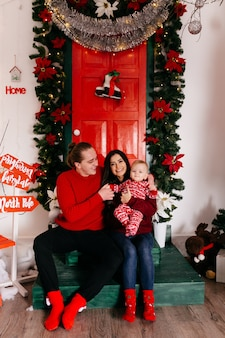 Счастливая семья улыбается в студии на фоне елки с подарком