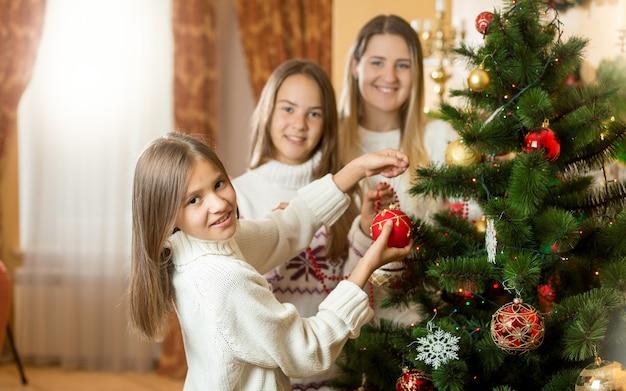 リビングルームでクリスマスツリーを飾る幸せな笑顔の家族